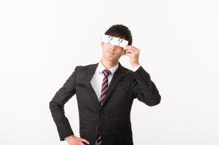 顔を隠している社会人男性