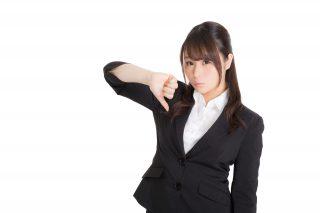 親指を下にする女性