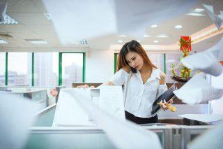 職場で忙しそうに働く女性