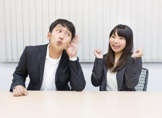 職場で楽しそうに話をする女性とそれを聞く男