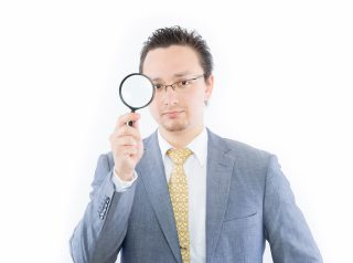 虫眼鏡で観察する男性