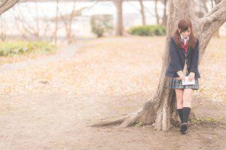木の下で佇む女子高生